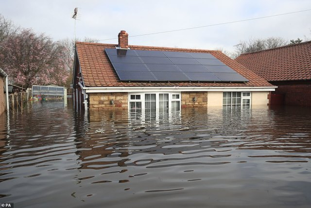 Floodwater surrounds the bungalow in which Kevin Lorryman lives in Snaith, East Yorkshire, this morning