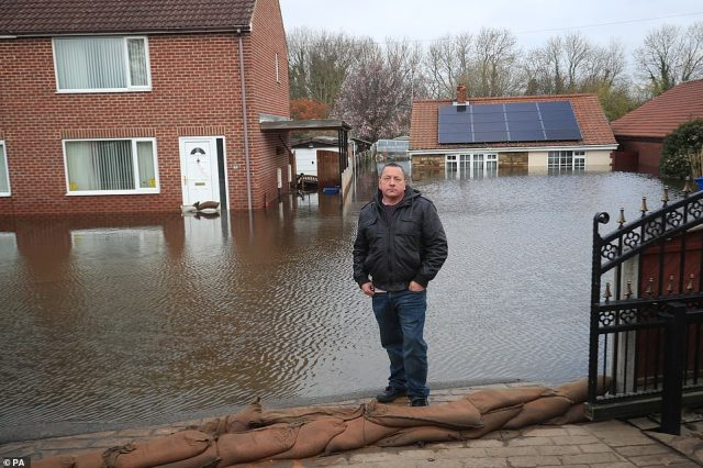 Kevin Lorryman outside his bungalow in Snaith, which is surrounded by floodwater this morning