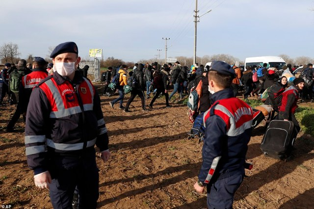 Migrants carrying their belongings pass next to Turkish policemen at a border crossing point with Greece as they are waved through after Turkey said it would no longer block them