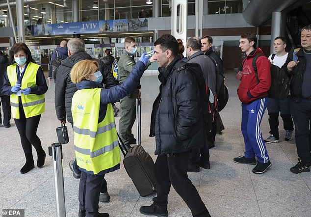 Health officials revealed a man tested positive after catching the deadly infection in Italy and travelling to Chernivtsi via Romania (airport workers atDanylo Halytskyi International Airport in Lviv, Ukraine, check the temperatures of travellers)