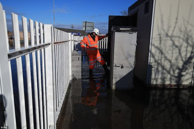 A Network Rail employee wades through floodwater in Snaith, East Yorkshire, today as dozens of flood warnings are in place