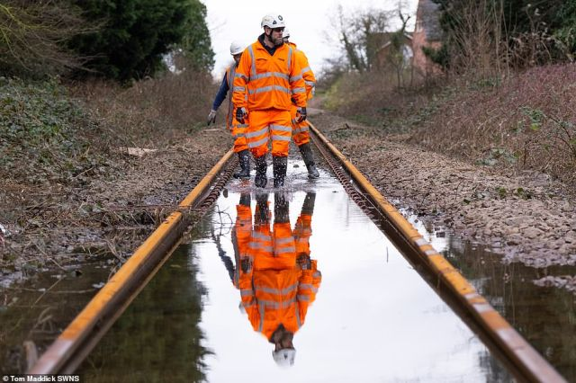 Workers inspect floodwater on a railway line in the village of Snaith in East Yorkshire today