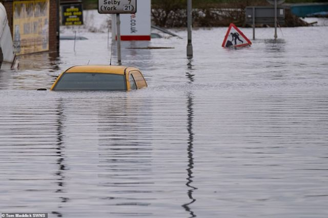 A car is almost completely submerged in the floodwater in the village of Snaith, East Yorkshire