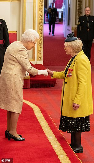 The gloved Queen shakes hands with Butterflies star Wendy Craig as she is made a CBE today