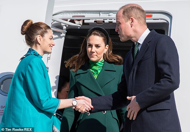 Prince William shakes hands with a member of cabin crew as he and Kate arriveat Dublin International Airport