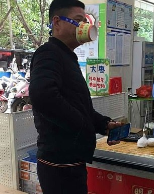 A man at a food kiosk, thought to be in China, left, tied an empty cardboard pot around his face as a barrier