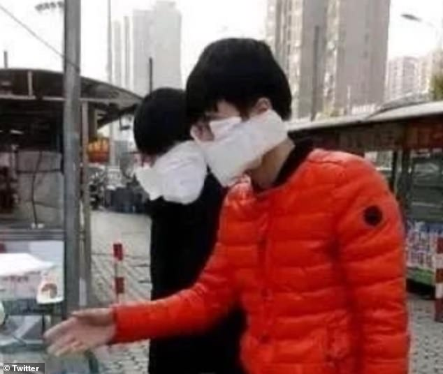 Two unidentified men wear white masks in China as fears over the coronavirus continues to grow around the world