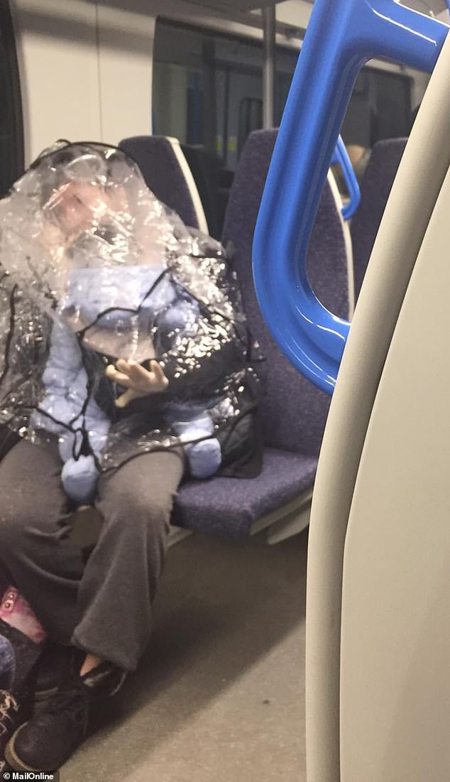 Extreme measures! One London passenger got creative by hiding under the rain cover for their baby's pushchair to shield them both