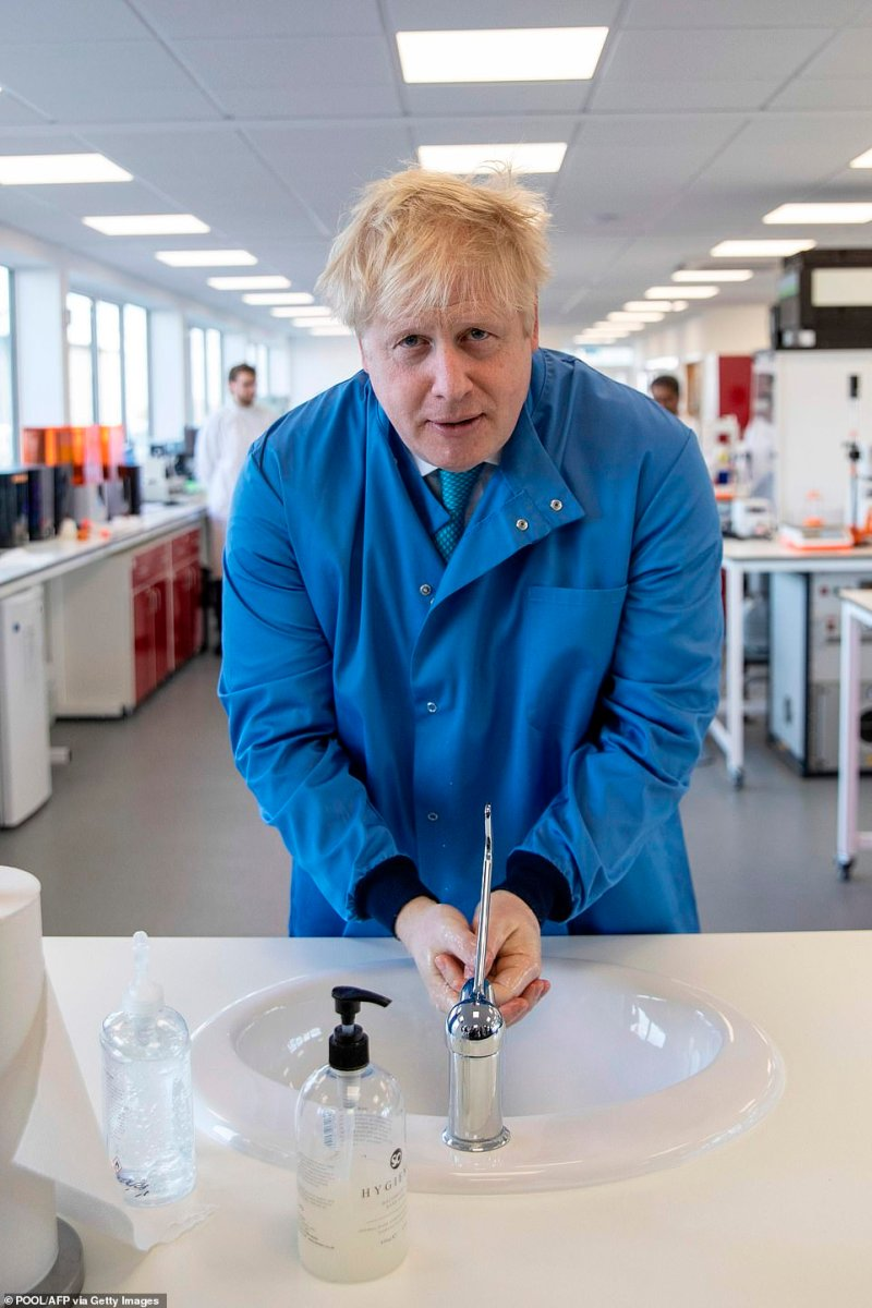 Britain's Prime Minister Boris Johnson washes his hands during a visit to the Mologic Laboratory in the Bedford technology Park, north of London on Friday