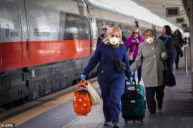 Passengers depart from a train in Naples arriving from Milan as people scrambled to flee from quarantined regions yesterday