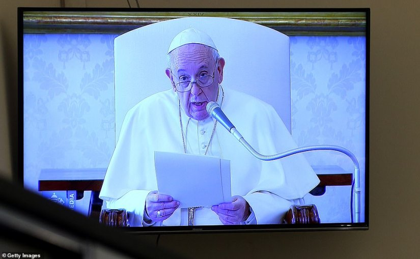 Pope Francis, believed to have tested negative for coronavirus last week, speaks today as seen on a Vatican screen