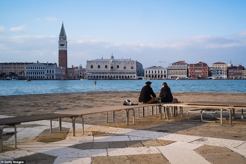 Two people face a largely deserted Venice - a city that most commonly suffers from the opposite problem of overcrowding