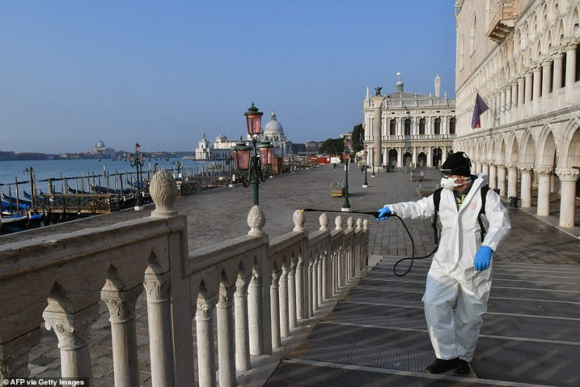 A municipal health worker wearing a protective suit and face masks sprays disinfectant on a barrier today in Venice