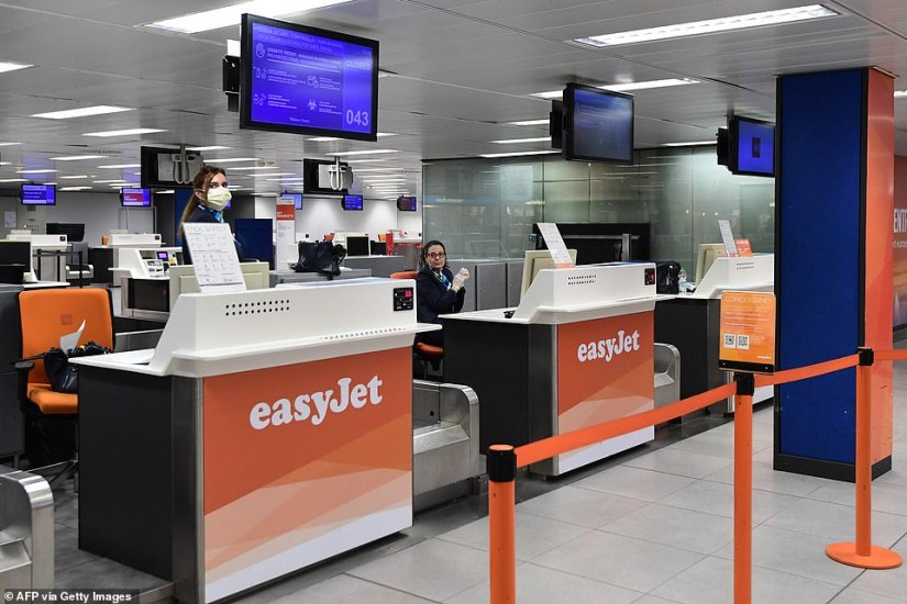 Staff are sitting behind an easyJet counter, a woman wearing a mask, at Milan Linate airport today - with many countries imposing restrictions on travel to and from Italy