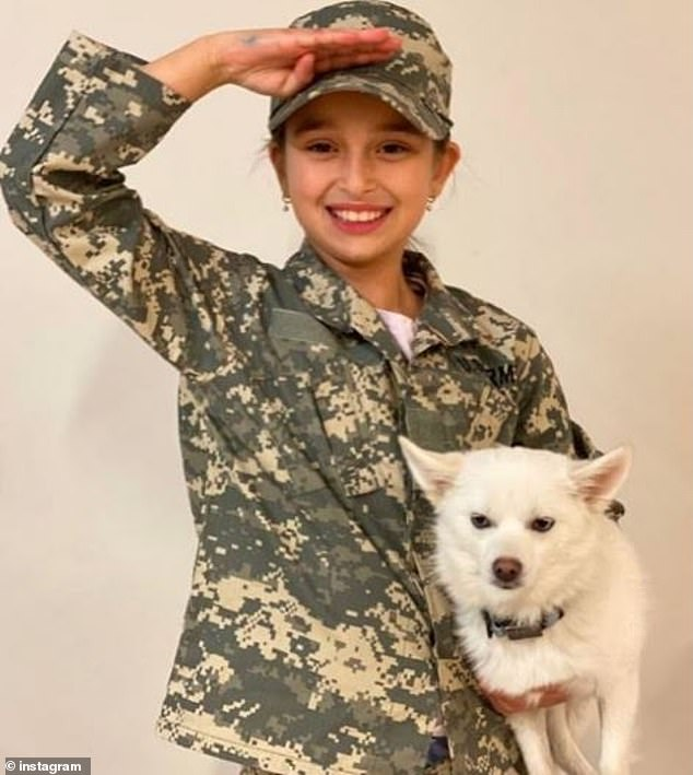 Too cute: Among the images was an adorable photo of Arabella posing with her dog, Winter, while modeling camouflage fatigues