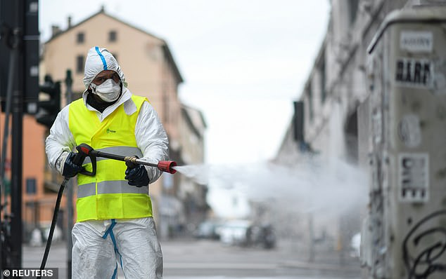 Travel across the 51 states has been partially suspended to curb the epidemic which largely stemmed from an outbreak in northern Italy. Pictured, a worker sanitising the streets of Milan