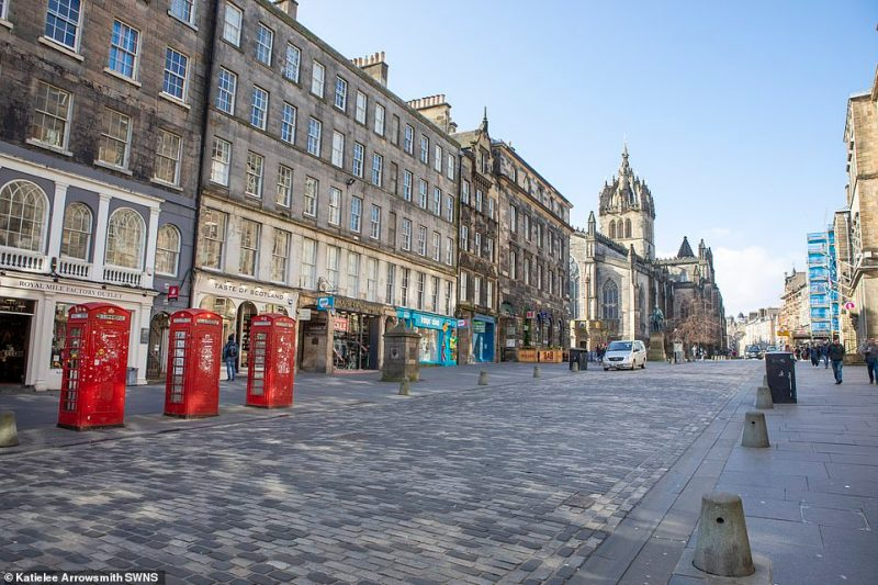 Edinburgh's Royal Mile is pictured almost deserted today after the Scottish Government yesterday announced it would ban large gatherings from next week