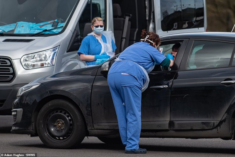 People get swabbed at a drive-through coronavirus testing station set up near a branch of KFC in Wolverhampton. People who think they might have the virus have been told to avoid the city's hospital