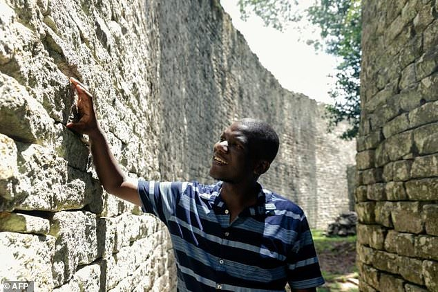Archaeological curator Munyaradzi Sagiya walks in a corridor by a conical tower. Parts of the structure, at least eight centuries old, compare with the majesty of the Giza Pyramids