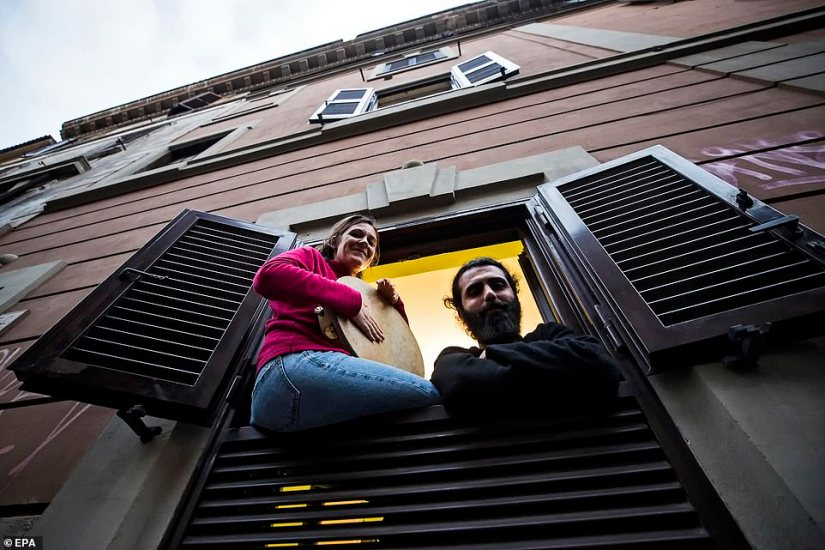 People sing from their home windows during a flash mob launched across Italy to bring people together in Rome