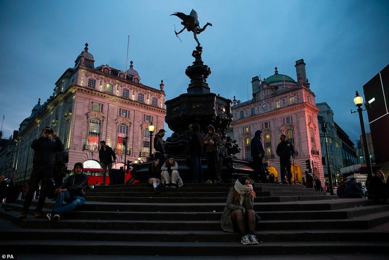 People sit on the steps of Piccadilly Circus in London, on a quiet Saturday night after the Prime Minister said that Covid-19 'is the worst public health crisis for a generation'