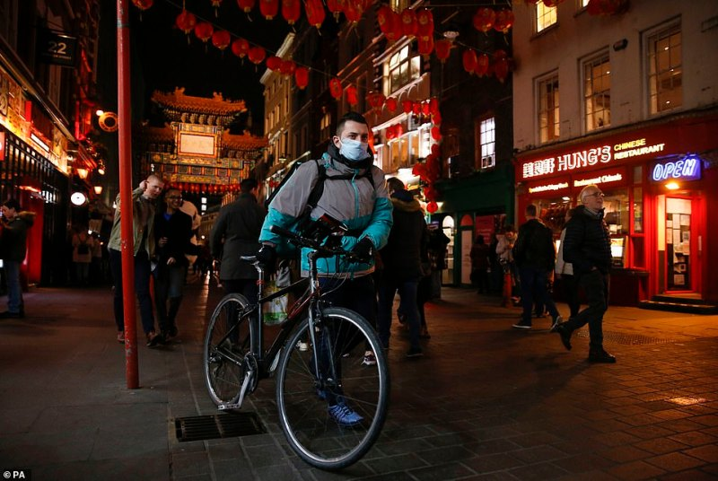 A Deliveroo rider wears a mask in Chinatown, London, after the food delivery service started offering contact free drop offs where riders drop food to your door step