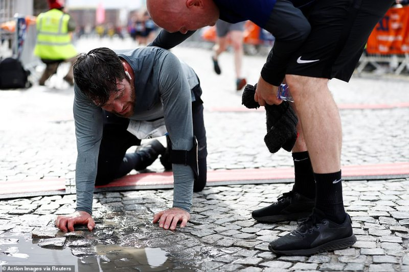 A runner falls to the floor after the race as the marathon goes ahead despite 14 cases of coronavirus in the Merseyside area