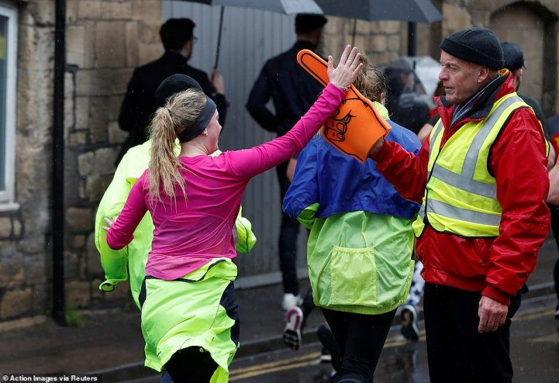 High five! A steward uses a foam hand to high five competitors as they pass on the course