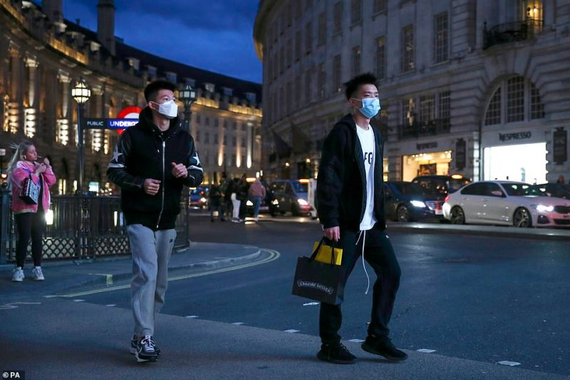 Two pedestrians cross the street wearing masks in Piccadilly Circus, London, after shopping