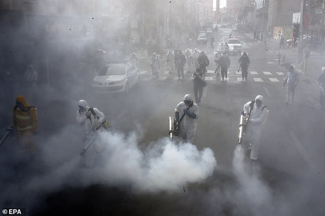 Iran is struggling to contain the worst outbreak in the Middle East, as Monday saw the biggest one-day rise in the death toll since the epidemic began, taking the total to 853. Pictured,Iranian Firefighters disinfect streets in an effort to stop the wild spread of coronavirus COVID-19 in Tehran, Iran, on March 13