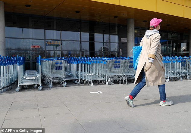 A woman walks past shopping trolleys in front of a closed Ikea store in Berlin today