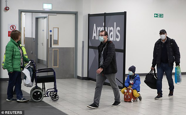Two men and a child wearing face masks walk through London Luton Airport today