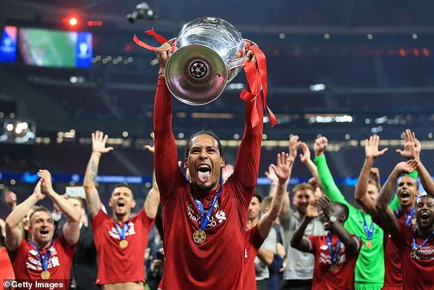 Van Dijk holding aloft the Champions League trophy after winning it with Liverpool last season