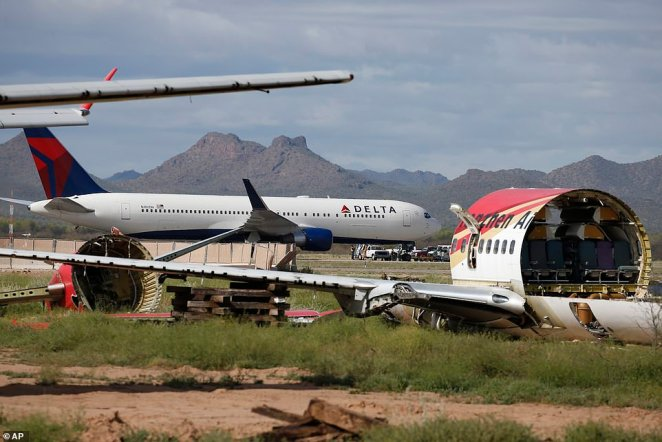 With a stripped passenger plane in the foreground, a recently landed Delta Air Lines airplane is worked on by ground crew