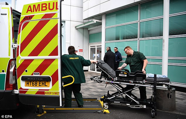 Nearly 20,000 fully qualified staff will be joining the NHS response to the pandemic, helping manage the expected surge in cases, in the first ever deal of its kind. Pictured: NHS staff outside a hospital in London