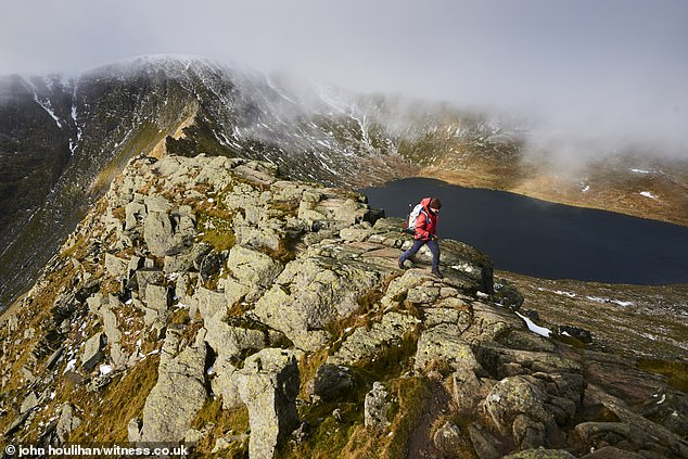 Well-trodden route: Mr Bennett on his way to the summit.About 250,000 people climb Helvellyn, England's third highest mountain and one of the Lake District's most popular attractions, every year