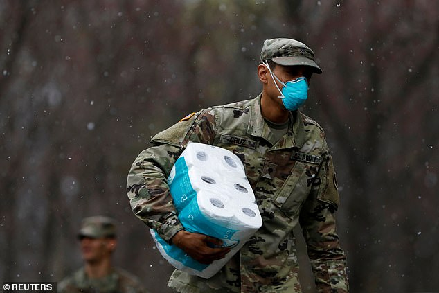 The National Guard has been deployed to help New York deal with its inundation of coroanvirus patients. FEMA is setting up 1,000 hospital beds at the Javits Center in Midtown. Pictured: A National Guard member delivers toilet paper in New Rochelle, New York