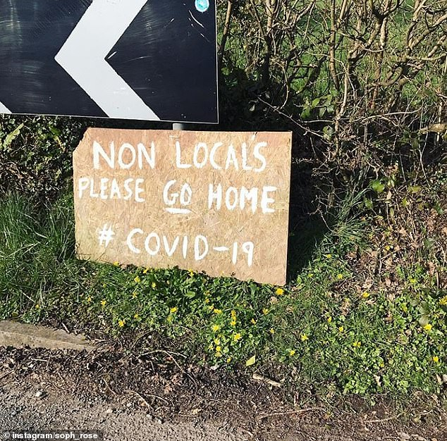 Country dwellers explode city residents who flee to places like London for idyllic retreats (in the photo, a person erected a roadside sign near Pembrokeshire)
