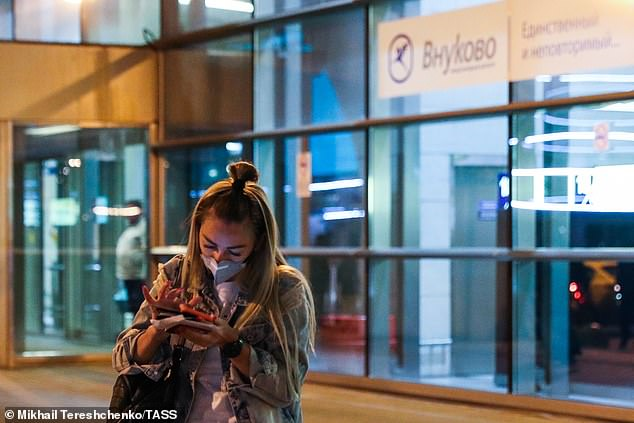 A woman types a text message on her phone as she stands outside theVnukovo International Airport