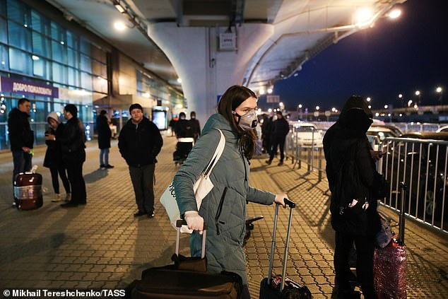 Travellers gather outside he airport in Moscow, Russia amid the growing coronavirus crisis