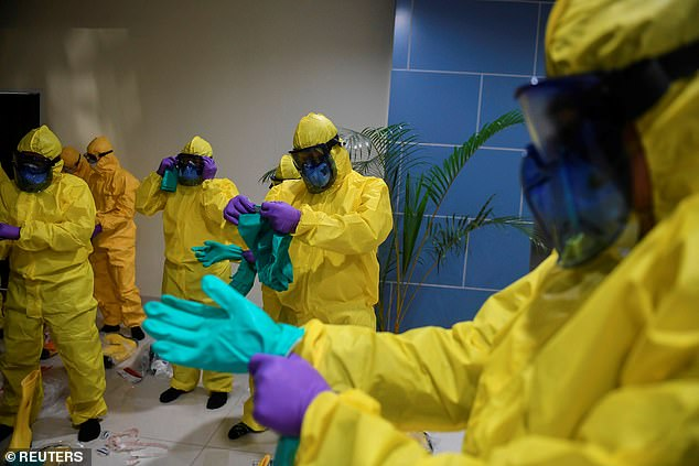 The passengers whose rooms were found to have new traces of the coronavirus had showed symptoms or were asymptomatic. Health officials are pictured suiting up in protective gear to treat passengers from the Diamond Princess on March 1