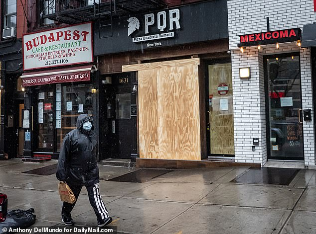An Upper East Side resident walks past PQR Pizza Quadrata Romana located on 1631 2nd Avenue in Manhattan, closed and closed due to Monday's COVID-19 pandemic