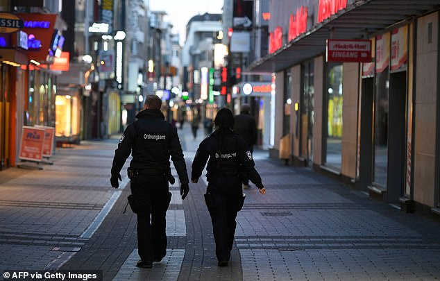 Security personnel keep people away from the streets of Cologne in western Germany while the country fights the coronavirus pandemic