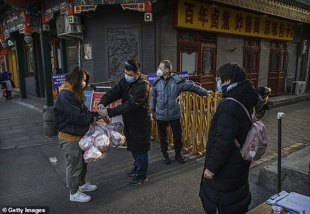 A Chinese restaurant has put up a huge banner to celebrate the 'coronavirus epidemic in the US and Japan' during the pandemic.A Chinese woman is seen wearing a protective mask as she has her temperature and identification checked in Beijing