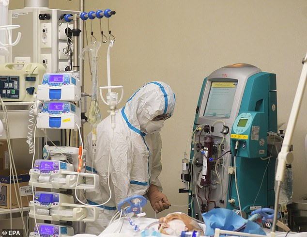 A medical professional works next to the bedside of a patient who is surrounded today by medical equipment at the Milan hospital