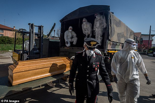 A uniformed soldier wearing gloves and a mask walks away from a truck where personnel in protective suits loaded the coffins from a depot in Ponte San Pietro