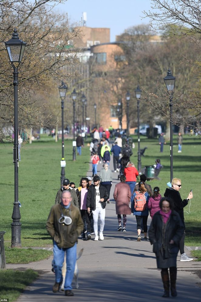 Pedestrians walk across Clapham Common in south London, despite government advice to stay at home where possible