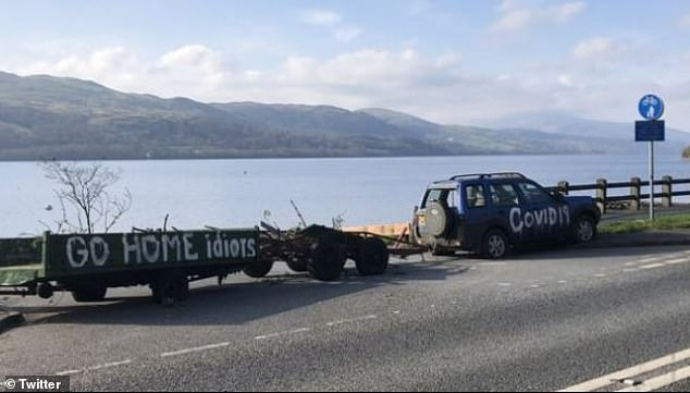 A car with a warning scrawled on one side was dragged through the entrance to a parking lot in Bala, Wales