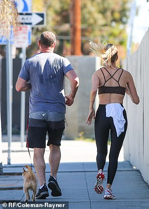 Taylor wore a sports bra and black leggings while Liev jogged along with their pet dog