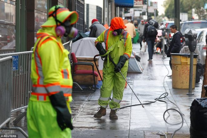 Workers sanitize streets where homeless people were living on March 20 in San Francisco